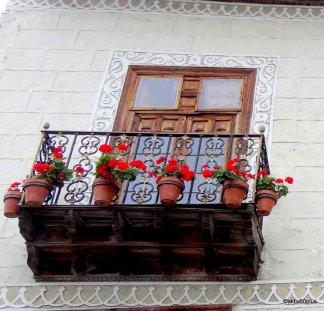 Die verzierten Holzfenster sind ebenfalls eine Augenweide, dazu die hübsche Präsentation der Geranien!